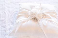 Gold wedding rings on satin pillow. Small pillow for wedding rings Royalty Free Stock Photo