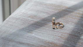 Gold wedding rings on a table close-up. Gold wedding rings on a wooden table close-up stock video footage