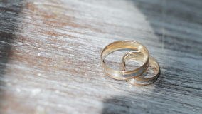 Gold wedding rings on a table close-up. Gold wedding rings on a wooden table close-up stock footage