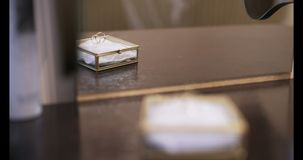 Gold wedding rings on table - love background. Shoot of two wedding rings in a box on table stock footage