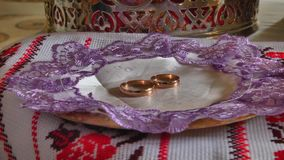 Gold wedding rings. Two gold wedding rings in the church during the wedding ceremony stock video footage