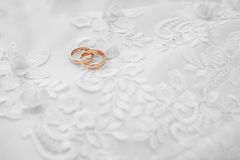 Gold wedding rings on white dress Royalty Free Stock Photo