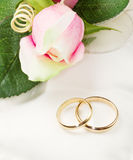 Gold wedding rings on white pillow with rose Stock Image