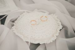 Gold wedding rings on a white satin pillow Royalty Free Stock Photos