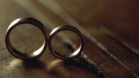 Gold wedding rings on a wooden floor in backlight macro closeup lens flare shoot diamond jewellery. Jewellery macro highlight wedding rings couple symbol of stock video footage