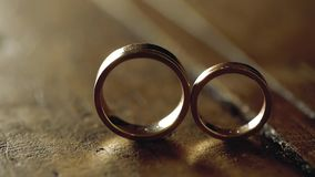 Gold wedding rings on a wooden floor in backlight macro closeup lens flare shoot diamond jewellery. Jewellery macro highlight wedding rings couple symbol of stock footage