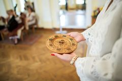 Gold wedding rings on a wooden rounded plate in the hands of a woman. Gold wedding rings on a wooden rounded plate in the hands of woman Royalty Free Stock Photography