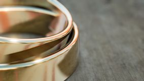Gold wedding rings on wooden table 3d illustration. With copy space stock illustration