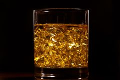 The gold of whiskey. Golden hard liquor with ice on the wooden table stock image