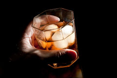 Gold whiskey in hand Stock Photos
