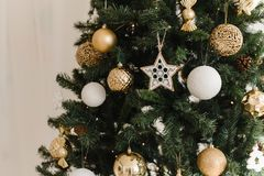 Gold and white Christmas ball on a Christmas tree in a light interior against the background of burning garlands of lights.