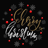 Gold and white handwritten calligraphic inscription Merry Christmas with pattern of red berry and snowflakes.  Royalty Free Stock Photo