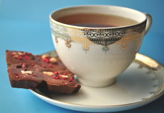 Gold and white porcelain tea cup and saucer with artisan chocolate on bright blue background with copy space Stock Image