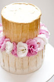 Gold and white wedding cake. And pink flowers on top Royalty Free Stock Photography