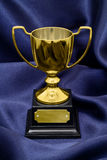 Gold Winners trophy on silk background. A Gold Winners trophy on a blue silk background great concept for achievement, success or winning a competition or award stock images