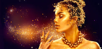 Gold woman skin. Beauty fashion model girl with golden makeup. Hair and jewellery on black background royalty free stock photo