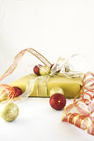 Gold Wrap Red Ribbon Christmas Present. Gift wrapped with golden paper and red and golden ribbons. The gift is surrounded by gold and red Christmas ornaments on Stock Photos