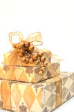 Gold wrapped Christmas present. Stacked Christmas gifts, wrapped in gold Stock Image
