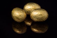 Gold wrapped easter eggs. Chocolate easter eggs wrapped in gold colored aluminium foil with reflection against black background stock photography