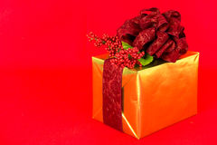 Gold-wrapped Gift with Red Damask Ribbon. A gift wrapped in gold foil is topped with a dark red, damask bow and ribbons and red berries decoration royalty free stock image
