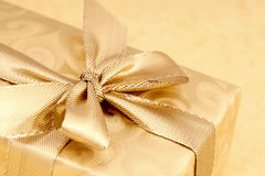 Gold wrapped gift with ribbon. Stock Image