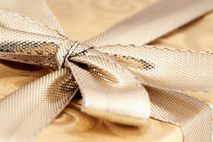 Gold wrapped gift with ribbon. Royalty Free Stock Photos