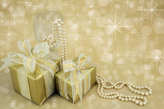 Gold wrapped presents with pearls. Gold wrapped presents with wine glass and pearls Royalty Free Stock Images