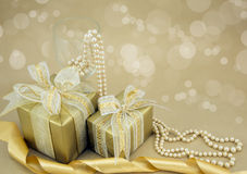 Gold wrapped presents with pearls. Gold wrapped presents with wine glass and pearls Royalty Free Stock Photos