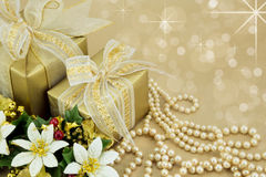 Gold wrapped presents with pearls and flowers Stock Photos
