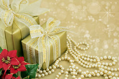 Gold wrapped presents with pearls and flowers. Gold wrapped presents with flowers and pearls Stock Image