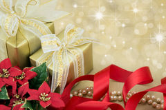 Gold wrapped presents with red ribbon and flowers Stock Photography