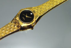 Gold Wrist Watch. A Gold wrist watch with black face and diamond on a mirror Stock Photos