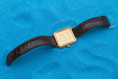 Gold wristwatch on a blue sand Stock Photography