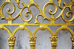 Goldalter bearbeiteter Zaun-Nahaufnahmehintergrund Geschmiedetes Golden Gate des aufwändigen schönen Musters Stockfotos