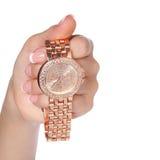 Goldarmbanduhren mit Diamanten in der weiblichen Hand lokalisiert Stockbilder