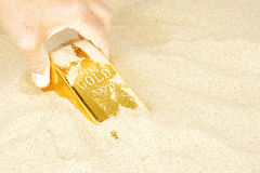 Goldbar in sand. Goldbar digged out of the sand Royalty Free Stock Photo