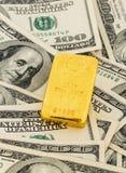 Goldbarren auf Dollarscheinen Lizenzfreies Stockfoto