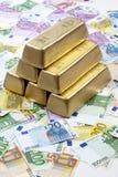 Goldbarren auf Haufen von Euroanmerkungen Stockfotos