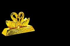 Goldbarren mit Schwandekoration lizenzfreie stockfotos