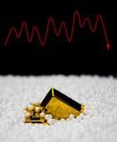 Goldbarren sinken in Polystyrenpartikel und in eine Schwankung auf Hintergrund stockfoto