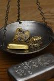 Goldbarren u. Nuggets in der Balancen-Skala - Silberbarren (Vordergrund) Lizenzfreies Stockbild