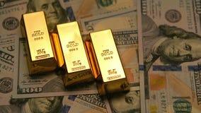 Goldbarren und -dollar auf einer Tabelle mit hellem zum dunklen Effekt stock video