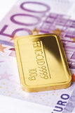 Goldbarren und Eurobanknote Stockbild