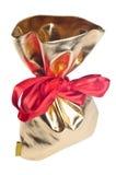 Goldbeutel mit Geschenken und einem roten Bogen Lizenzfreie Stockbilder