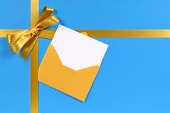 Goldbogen, Geschenkband, Weihnachtskarte im Umschlag, blauer Hintergrund Stockfoto
