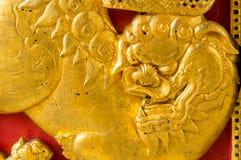 Goldchinesischer Löwe auf der roten hölzernen Tür Stockfoto