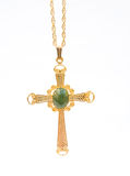 Goldchristliches Kreuz mit grünem Edelsteinstein. lizenzfreies stockfoto