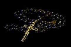Goldchristliches Kruzifix mit Rosenkranzperlen Lizenzfreies Stockfoto