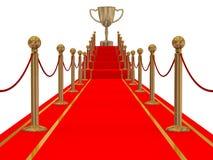 Goldcup des Siegers auf einem Pfad des roten Teppichs. Lizenzfreies Stockfoto