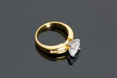 Golddiamantring auf dem reflektierenden Hintergrund Stockbild